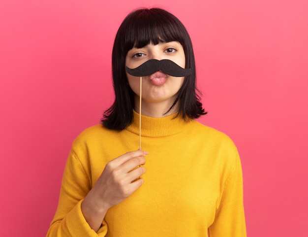 Blij jong donkerbruin kaukasisch meisje houdt nepsnor op stick
