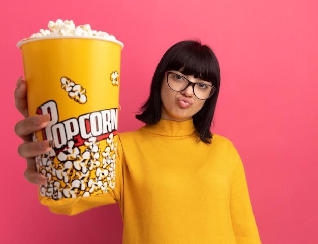 Blij jong donkerbruin kaukasisch meisje in optische glazen die popcornemmer houden