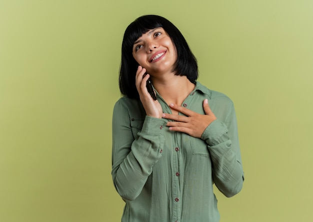 Blij jong donkerbruin kaukasisch meisje legt hand op borst die op telefoon spreekt en omhoog geïsoleerd op olijfgroene achtergrond met exemplaarruimte kijkt