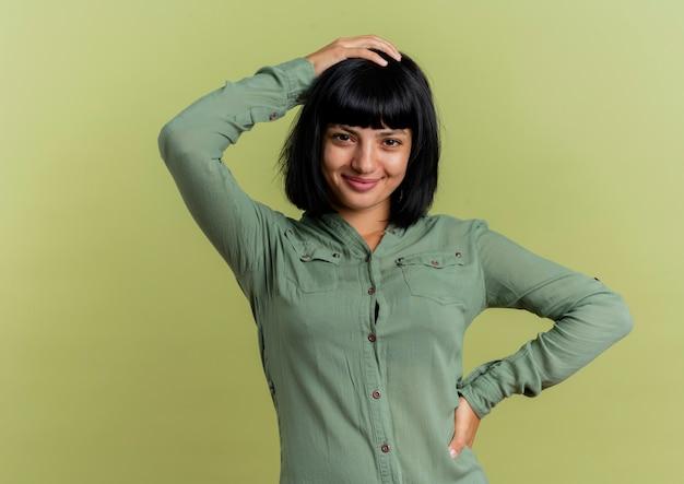 Blij jong donkerbruin kaukasisch meisje legt hand op taille en houdt hand op hoofd geïsoleerd op olijfgroene achtergrond met exemplaarruimte