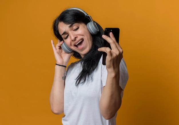 Blij jong donkerbruin kaukasisch meisje op hoofdtelefoons kijkt naar telefoon die selfie neemt die op oranje muur wordt geïsoleerd