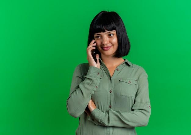 Blij jong donkerbruin kaukasisch meisjesbesprekingen over telefoon die kant bekijken die op groene achtergrond met exemplaarruimte wordt geïsoleerd