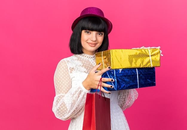 Blij jong feestmeisje met feestmuts met papieren zak en cadeaupakketten geïsoleerd op roze muur met kopieerruimte