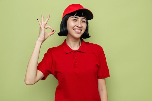 Blij jong kaukasisch bezorgmeisje dat ok teken gebaart