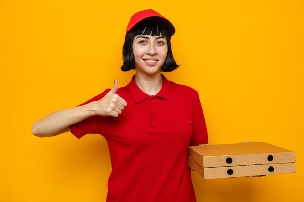 Blij jong kaukasisch bezorgmeisje dat pizzadozen vasthoudt en omhoog steekt