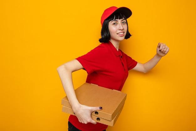 Blij jong kaukasisch bezorgmeisje dat zijwaarts staat met pizzadozen en doet alsof ze rent