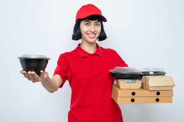 Blij jong kaukasisch bezorgmeisje met voedselcontainer en voedselverpakking op pizzadozen