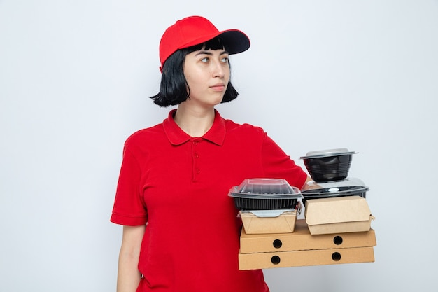 Blij jong kaukasisch bezorgmeisje met voedselcontainers en verpakkingen op pizzadozen die naar de zijkant kijken