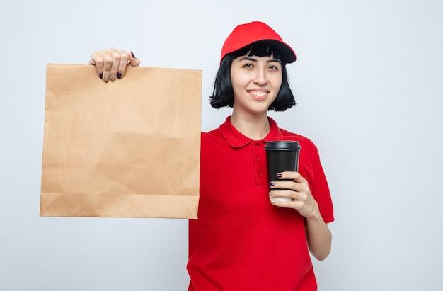 Blij jong kaukasisch bezorgmeisje met voedselverpakking en papieren beker kijkend naar de voorkant
