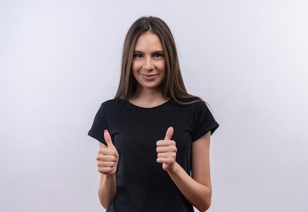 Blij jong kaukasisch meisje dat zwarte t-shirt draagt haar duimen omhoog op geïsoleerde witte achtergrond