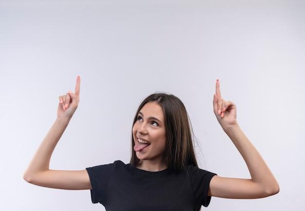 Blij jong kaukasisch meisje dat zwarte t-shirt draagt wijst naar het tonen van tong op geïsoleerde witte muur