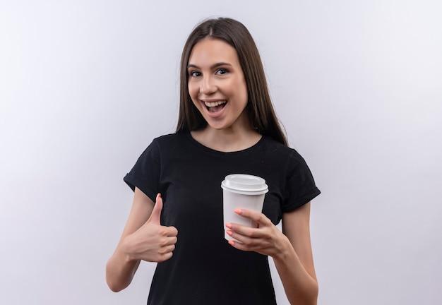 Blij jong kaukasisch meisje die zwarte t-shirt dragen die kop van koffie haar duim omhoog op geïsoleerde witte muur houden