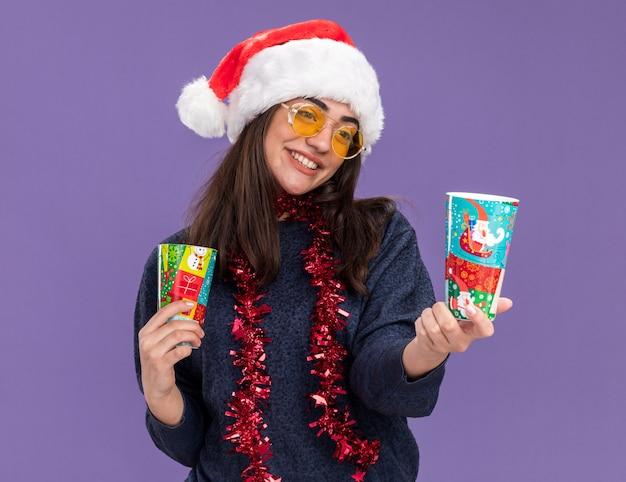 Blij jong kaukasisch meisje in zonnebril met kerstmuts en slinger om nek houdt en kijkt naar papieren bekers geïsoleerd op paarse muur met kopieerruimte
