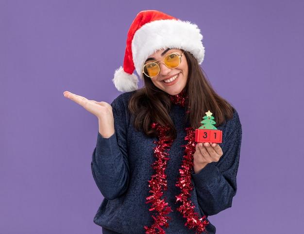 Blij jong kaukasisch meisje in zonnebril met kerstmuts en slinger om nek houdt kerstboomversiering en houdt hand open geïsoleerd op paarse muur met kopieerruimte