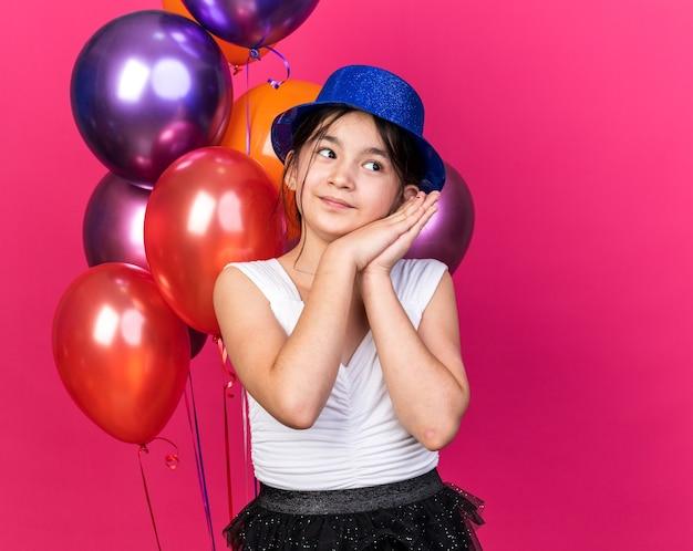 Blij jong kaukasisch meisje met blauwe feestmuts hand in hand en kijkend naar kant staande voor helium ballonnen geïsoleerd op roze muur met kopie ruimte
