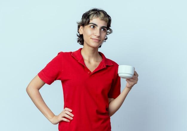 Blij jong kaukasisch meisje met de holdingskop van het pixiekapsel die kant bekijken die op witte achtergrond met exemplaarruimte wordt geïsoleerd