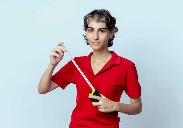Blij jong kaukasisch meisje met de meter van de de holdingsband van het pixiekapsel die op witte achtergrond wordt geïsoleerd