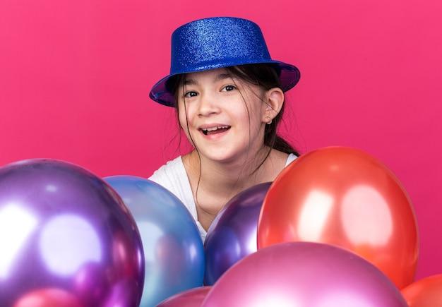 Blij jong kaukasisch meisje met een blauwe feestmuts die staat met heliumballonnen geïsoleerd op een roze muur met kopieerruimte