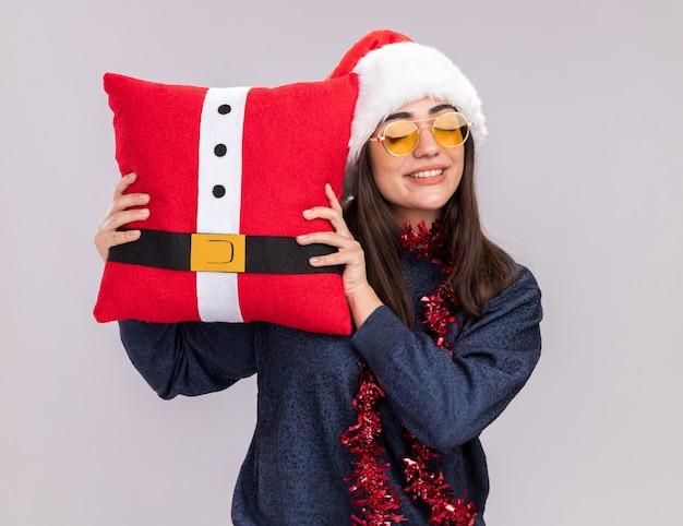 Blij jong kaukasisch meisje met kerstmuts en slinger om nek staat met gesloten ogen met versierd kussen geïsoleerd op een witte muur met kopieerruimte