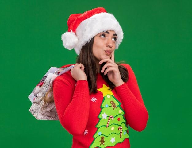 Blij jong kaukasisch meisje met kerstmuts legde vinger op kin en houdt papieren geschenkzak opzoeken geïsoleerd op groene achtergrond met kopie ruimte