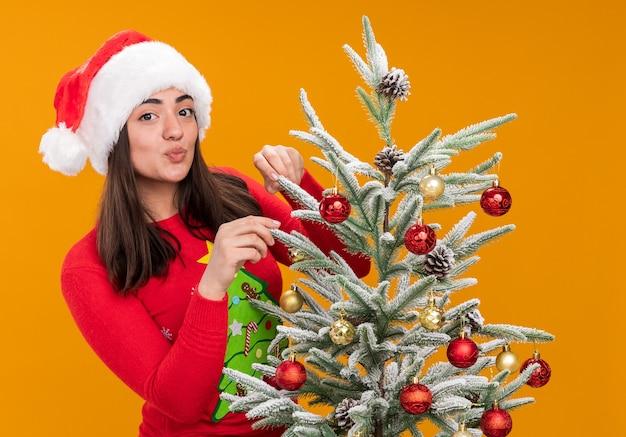 Blij jong kaukasisch meisje met kerstmuts versieren kerstboom geïsoleerd op een oranje achtergrond met kopie ruimte