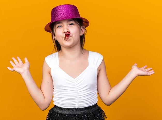 Blij jong kaukasisch meisje met paarse feestmuts blazend feestfluitje staande met opgeheven handen geïsoleerd op oranje muur met kopieerruimte
