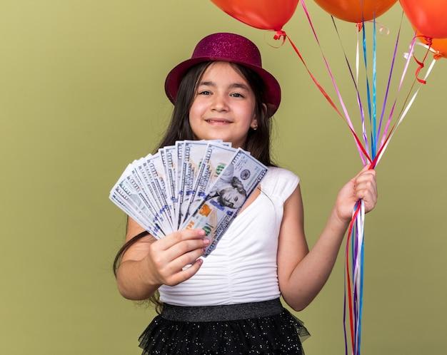 Blij jong kaukasisch meisje met paarse feestmuts met heliumballonnen en geld geïsoleerd op olijfgroene muur met kopieerruimte