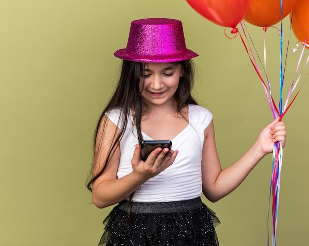 Blij jong kaukasisch meisje met paarse feestmuts met heliumballonnen en kijkend naar telefoon geïsoleerd op olijfgroene muur met kopieerruimte