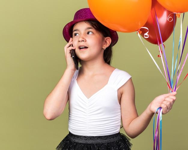 Blij jong kaukasisch meisje met paarse feestmuts met heliumballonnen pratend aan de telefoon kijkend naar kant geïsoleerd op olijfgroene muur met kopieerruimte