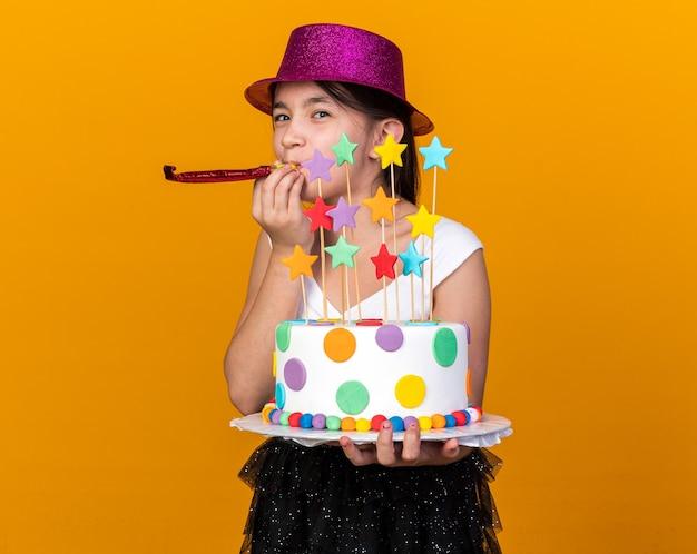 Blij jong kaukasisch meisje met paarse feestmuts met verjaardagstaart en blazend feestfluitje geïsoleerd op oranje muur met kopieerruimte