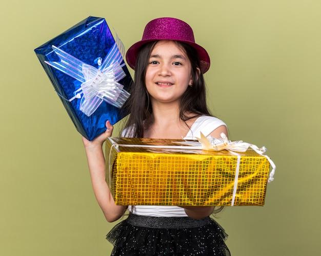 Blij jong kaukasisch meisje met paarse feestmuts stak geschenkdozen geïsoleerd op olijfgroene muur met kopie ruimte
