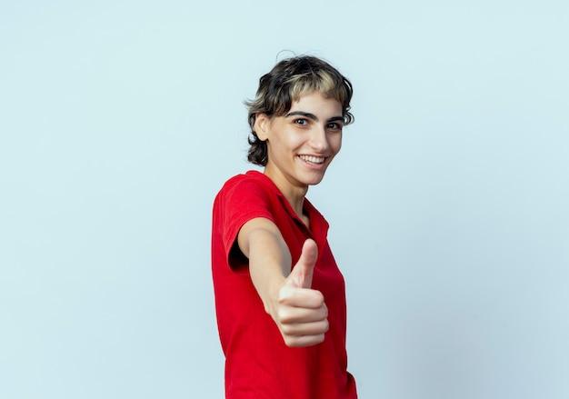 Blij jong kaukasisch meisje met pixiekapsel dat uit hand uitrekt en duim toont die op camera op witte achtergrond met exemplaarruimte wordt geïsoleerd