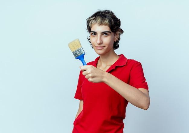 Blij jong kaukasisch meisje met pixiekapsel dat verfborstel naar camera uitrekt die op witte achtergrond met exemplaarruimte wordt geïsoleerd