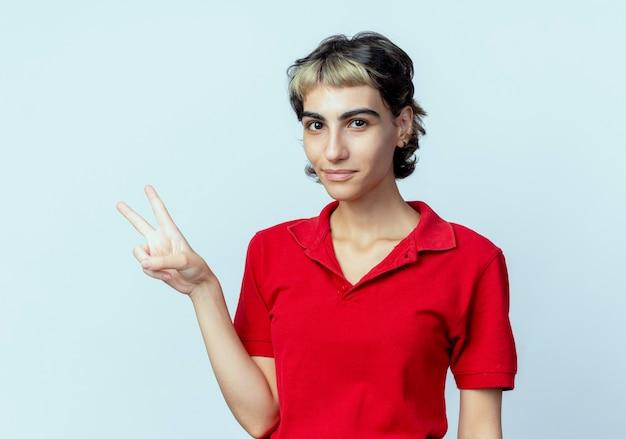 Blij jong kaukasisch meisje met pixiekapsel dat vredesteken doet dat op witte achtergrond wordt geïsoleerd