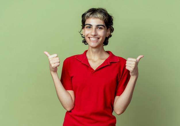 Blij jong kaukasisch meisje met pixiekapsel die duimen tonen die omhoog op olijfgroene achtergrond met exemplaarruimte worden geïsoleerd