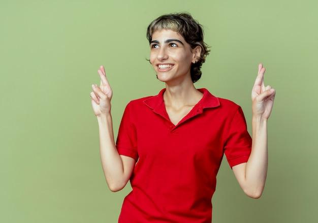 Blij jong kaukasisch meisje met pixiekapsel die gekruiste vingersgebaar doen die kant bekijken die op olijfgroene achtergrond met exemplaarruimte wordt geïsoleerd