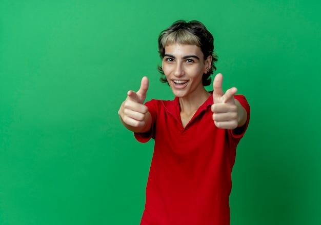 Blij jong kaukasisch meisje met pixiekapsel die op camera richten die op groene achtergrond met exemplaarruimte wordt geïsoleerd