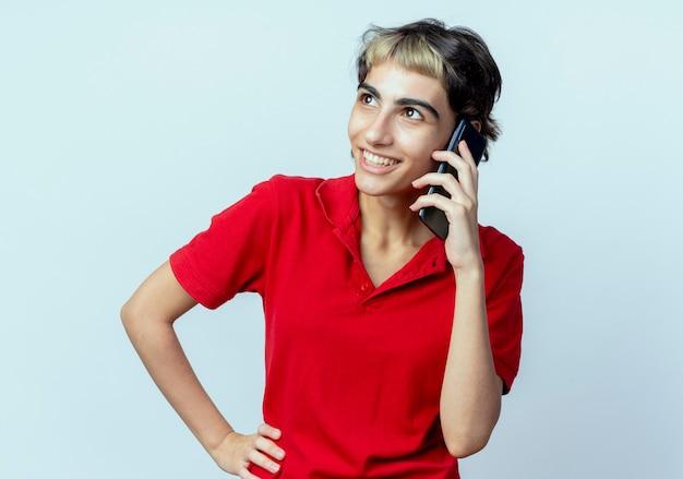 Blij jong kaukasisch meisje met pixiekapsel die op telefoon spreken die hand op taille zetten die op witte achtergrond wordt geïsoleerd