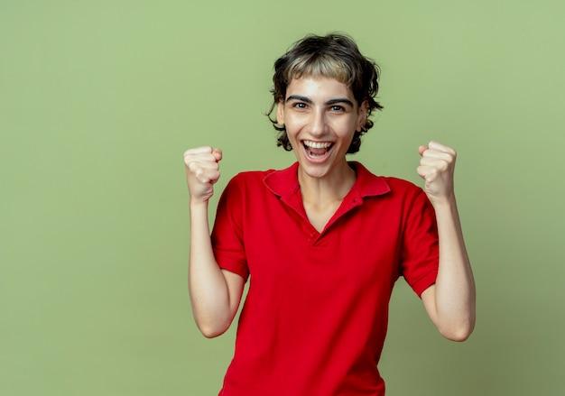 Blij jong kaukasisch meisje met pixiekapsel die vuisten balde die op olijfgroene achtergrond met exemplaarruimte wordt geïsoleerd