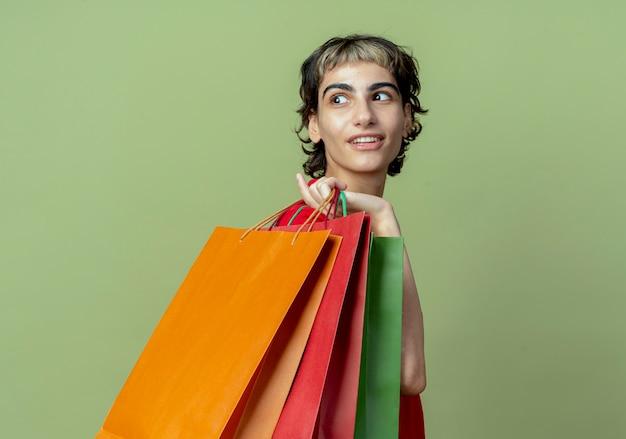 Blij jong kaukasisch meisje met pixiekapsel die zich in profielmening bevinden die boodschappentassen op schouder houden die achter geïsoleerd op olijfgroene achtergrond met exemplaarruimte kijken
