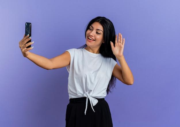 Blij jong kaukasisch meisje werpt hand omhoog houden en telefoon bekijken
