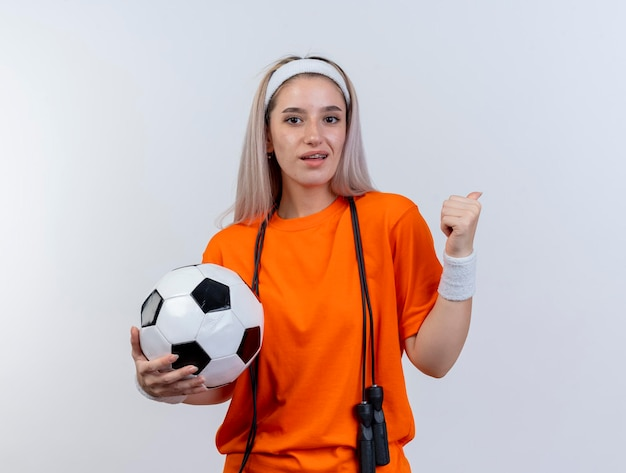 Blij jong kaukasisch sportief meisje met beugels en met touwtjespringen om de nek