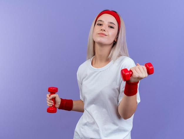 Blij jong kaukasisch sportief meisje met steunen die hoofdband dragen