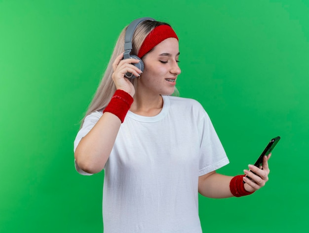 Blij jong kaukasisch sportief meisje met steunen op hoofdtelefoons