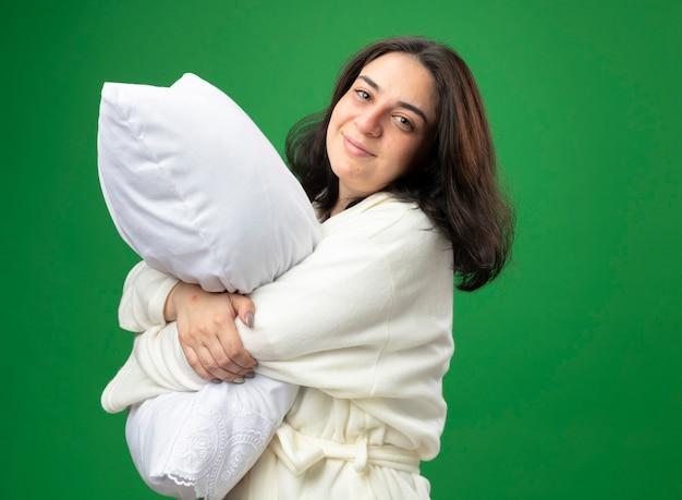 Blij jong kaukasisch ziek meisje die gewaad dragen die zich in profielmening bevinden die hoofdkussen koesteren die camera bekijken die op groene achtergrond met exemplaarruimte wordt geïsoleerd