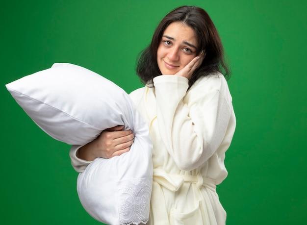 Blij jong kaukasisch ziek meisje die het hoofdkussen van de gewaadholding dragen die hand op gezicht houden die camera bekijken die op groene achtergrond wordt geïsoleerd