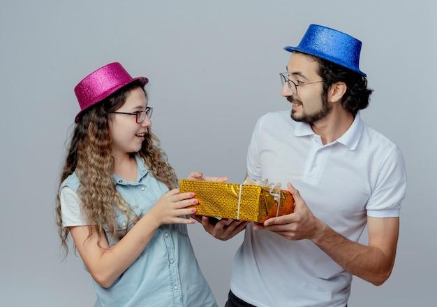 Blij jong koppel kijken elkaar dragen roze en blauwe hoeden met geschenkdoos