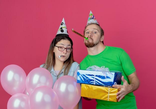 Blij jong koppel met feestmuts kijkt blazend fluitje man houdt geschenkdozen en meisje houdt helium ballonnen geïsoleerd op roze muur