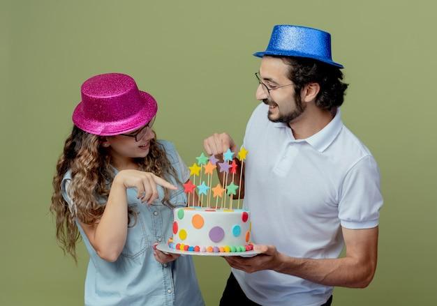 Blij jong koppel met roze en blauwe hoed kijken elkaar aan en wijst naar de verjaardagstaart in de hand van de man