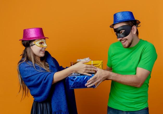 Blij jong koppel met roze en blauwe hoeden zetten maskerade oogmaskers op en kijken elkaar aan met geschenkdozen geïsoleerd op een oranje muur